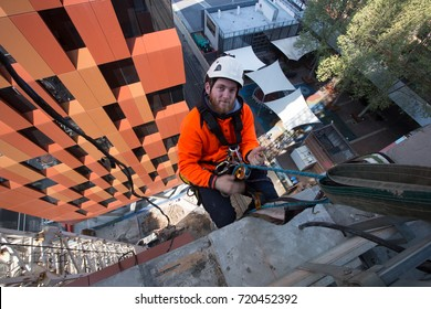 Male worker using Dynamic twins rope safety harness hardhat, abseiling from high rise building, working at height in Sydney city Australia.,