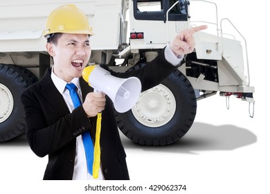 Male worker using a megaphone for screaming with a big truck on the background, isolated on white background