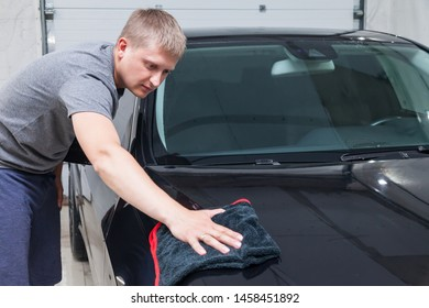 A male worker washes a black car, wiping water with a soft cloth and microfiber, cleaning the surface to shine in a vehicle detailing workshop. Auto service industry.