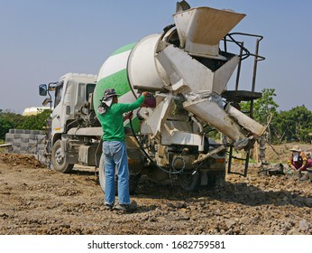 A male worker washing / cleaning a cement mixer truck after finish pouring out the concrete