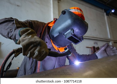 Male  worker wearing protective clothing of repair pipe stainless argon welding industrial construction