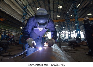 Male  worker wearing protective clothing of butt weld pipe carbon steel argon welding industrial construction
