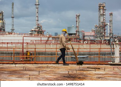 Male  worker wearing protective clothing cleaning roof oil storage tank industrial construction
