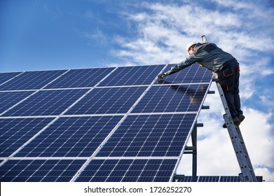 Male worker in white safety helmet standing on ladder and repairing photovoltaic solar panel station under beautiful blue cloudy sky. Concept of alternative sources of energy.