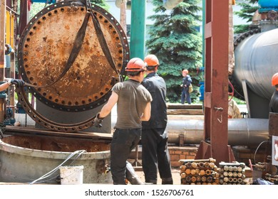 Male workers assemblers mount a shell-and-tube heat exchanger, repair equipment at an oil refining petrochemical chemical industrial plant during a scheduled shutdown repair.
