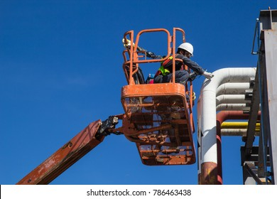 Male workers in a boom lift of thickness pipeline oil inspection.