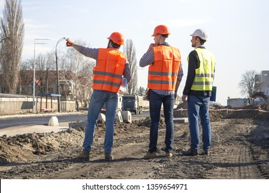 male workers engineers at a construction site with the head in helmets look at the house that is being built