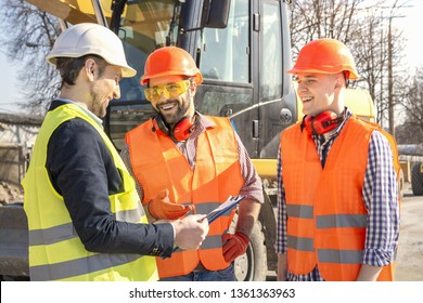 male workers engineers in helmets talking near the bulldozer and excavator