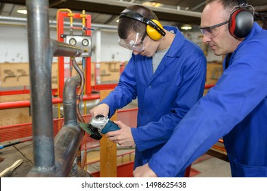 male workers in protective clothing holding ear protectors at factory