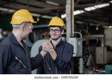 male workers and protective uniform shaking hands while working success teamwork collaboration. Two colleagues at a factory