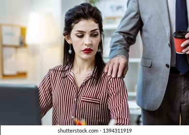 Male workmate interrupting. Office worker in grey costume and cup of coffee touching female colleague while she being busy
