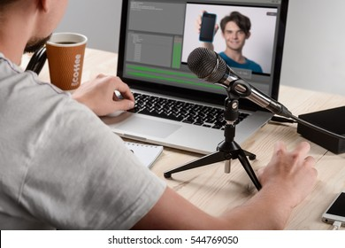 Male works as blogger and cuts a review for his channel with comments about new smartphone. Professional microphone on a holder near the modern laptop with wi-fi connection.