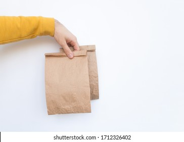 Male in a yellow sweater hold in hand several brown clear empty blank craft paper bags for give takeaway isolated on white background. Copy space. Advertising area.