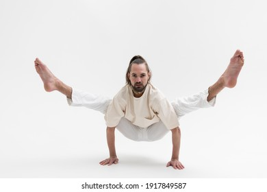 Male yoga teacher practicing in studio. Man isolated on white background doing a handstand