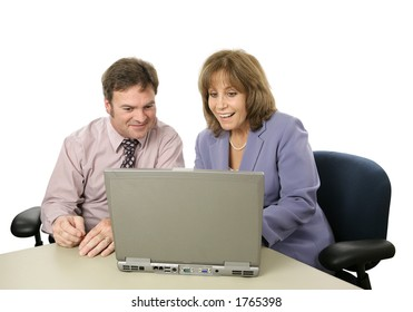 A male-female business team happy about what they see on the computer.  Isolated.