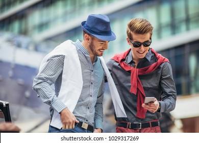 Males beautiful models outdoors using phone, city style fashion