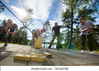 Males And Females Picking Up Wooden Blocks With Ropes