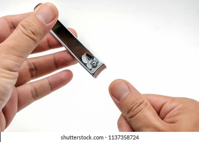 Male's hand holding on nail clippers,Man use nail clipper cutting their thumbs nail