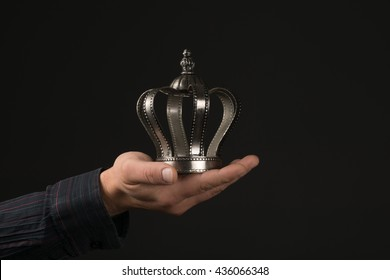 males Hand holding a silver Crown before gray Background