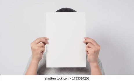 Male's hands is holding the A4 paper and wear gray t shirt on white background.