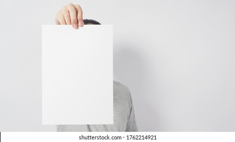 Male's hands is holding the A4 paper and wear gray t shirt and standing on white background.