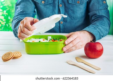 Males hands opening lunchbox with rice and mixed vegetables on white wooden background; selective focus