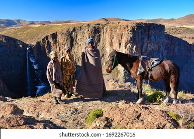 Maletsunyane Falls, Semonkong, Kingdom of Lesotho, Africa – 26th of July 2019: Three young boys from Basotho people with our horse, traditionally dressed with tribal blankets.