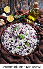 Malfouf Salad, Lebanese Cabbage Slaw with lemon juice, olive oil, garlic, and mint in an earthenware bowl with brown cloth and ingredients on a rustic table, vertical view from above