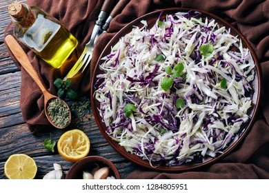 Malfouf Salad, Lebanese Cabbage Slaw with lemon juice, olive oil, garlic, and mint in an earthenware bowl with brown cloth and ingredients on a rustic table, horizontal view from above, close-up