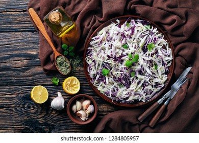 Malfouf Salad, Lebanese Cabbage Slaw with lemon juice, olive oil, garlic, and mint in an earthenware bowl with brown cloth and ingredients on a rustic table, flatlay, view from above