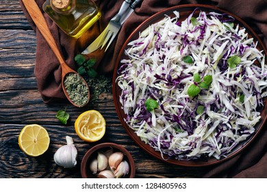 Malfouf Salad, Lebanese Cabbage Slaw with lemon juice, olive oil, garlic, and mint in an earthenware bowl with brown cloth and ingredients on a rustic table, flatlay, view from above, close-up