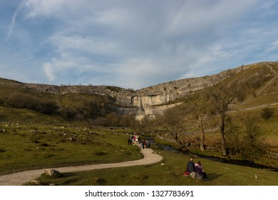 Malham Tarn, United Kingdom - February, 23, 2019:  Tourists walking along the path going towards Malham Cove cliff.