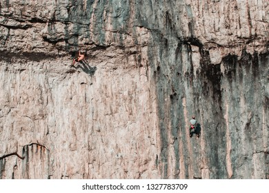 Malham Tarn, United Kingdom - February, 23, 2019: Wide shot of two men climbing the face of malham cove.