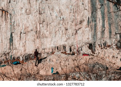 Malham Tarn, United Kingdom - February, 23, 2019: A man at the bottom of malham cove cliff face keeping climbers safe.