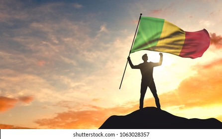 Mali flag being waved by a man celebrating success at the top of a mountain. 3D Rendering