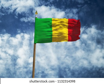 Mali flag Silk waving flag of Mali  made transparent fabric with wooden flagpole gold spear on background sunny blue sky white smoke clouds real retro photo Countries of world 3d illustration