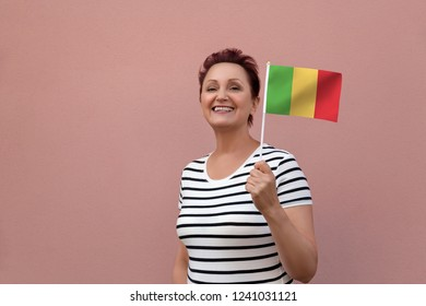 Mali flag. Woman holding Mali flag. Nice portrait of middle aged lady 40 50 years old with a national flag over pink wall background outdoors.