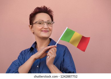 Mali flag. Woman holding Mali flag. Nice portrait of happy middle aged lady 40 50 years old with a national flag over pink wall background on the street outdoors.