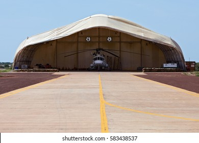 Mali, Timbuktu - August 11, 2016: Indonesian military mechanics team performs maintenance of MI-17 helicopter in soft-skin hangar at United Nation peacekeeping mission in Western Africa.
