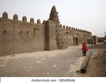 Mali, Timbuktu - August 13, 2016: View to the local street and side wall of restored Djingareyber Mosque that was mentioned in UNESCO List of World Heritage in Danger 2012.