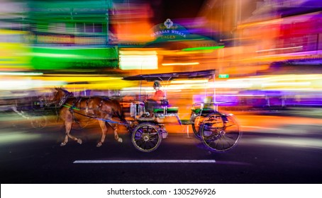 Maliboro Street Yogyakarta, Indonesia - July 23 2015 : Abstract panned image of a horse drawn cart commonly known as Andong or Dokar with colorful lights blurred across the frame.