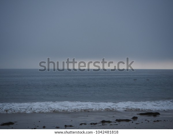 MALIBU BEACH, CALIFORNIA - JAN 05, 2018: Feeling lonely with the view of Malibu sea and grey sky