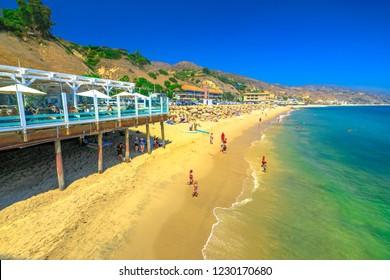 Malibu, California, United States - August 7, 2018: scenic coastal landscape with Santa Monica Mountains, Malibu Farm and turquoise sea of popular Carbon Beach or Billionaire Beach for houses of VIP.