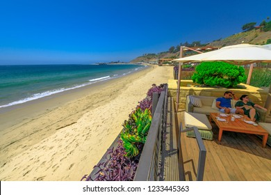 Malibu, California, United States - August 7, 2018: couple sitting at luxurious Japanese restaurant Nobu on famous Billionaire Beach or Carbon Beach for many famous people in Malibu. Summer holidays.