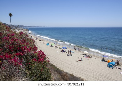 MALIBU, CALIFORNIA, USA - August 15, 2015:  Summer weekend beach goers enjoying the water Topanga State Beach in Santa Monica Bay.
