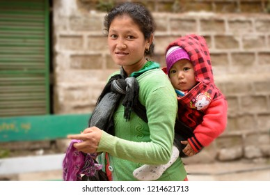 The MALL, Darjeeling, West Bengal/India: March 23, 2017: A Nepali mother carrying her little boy on the back and walking to drop him in the school. Most appreciating mom caring for her child.