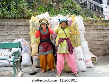 The MALL, Darjeeling, West Bengal/India: March 23, 2017: Two Nepali women working as a porter or labourer lifting sacks of cements with support on the hands