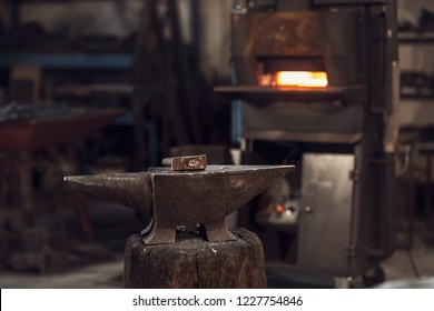 Mallet on an anvil in front of a red hot burning furnace in a metalworking workshop or blacksmith