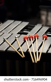 mallets sitting atop a xylophone with a dark background.