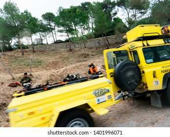 Mallorca, Baleares, Spain - May 10, 2018: Land Rover yellow Jeep SUV parked on a forest road with Incendis Forestals Fire Forest protection team of workers eating lunch near the road